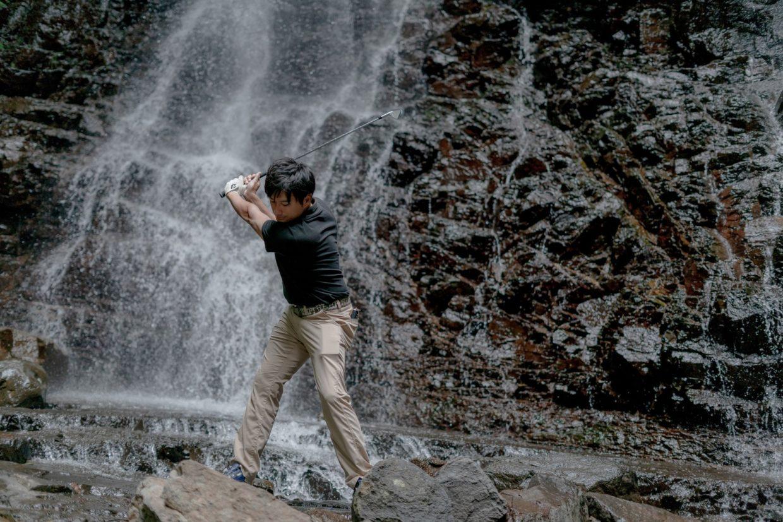滝の前で素振りするゴルファー
